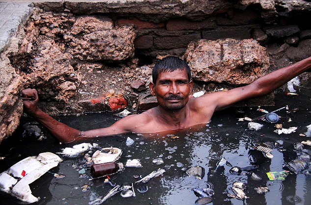 Indiano mergulha no esgoto e recebe R$ 9,50 por dia e uma garrafa de bebida alcoólica para trabalhar