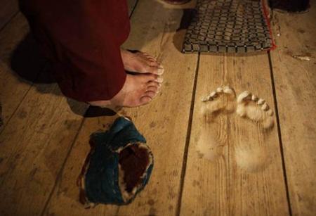 Monge budista faz pegadas no assoalho de madeira através de 20 anos de oração